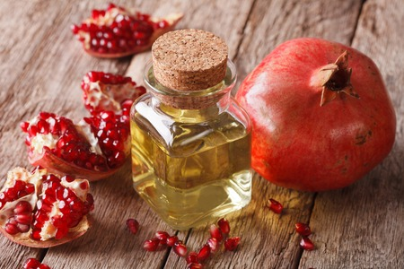 Pomegranate seed oil in a glass bottle on a table close-up. Horizontal Reklamní fotografie - 47414193