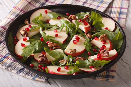 fruit salad: Healthy salad with apples, pomegranates, walnuts and rocket salad close-up on a plate. horizontal