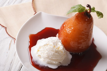 pear: Pear in wine sauce with vanilla ice cream close-up on a plate. horizontal view from above