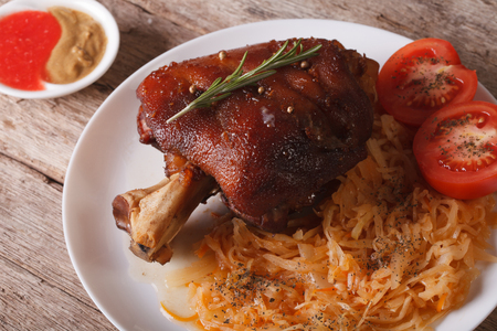 European cuisine: Baked pork knuckle and sauerkraut closeup on a plate. horizontal Stock Photo