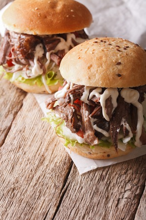 roast meat: Tasty Pulled pork sandwich with coleslaw and sauce close-up on the table. vertical