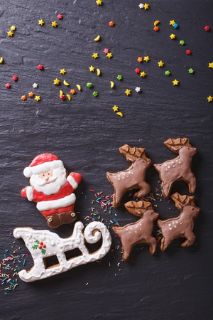 reindeer: Gingerbread Santa on a sleigh pulled by reindeers closeup. vertical view from above Stock Photo
