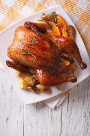 baked whole chicken with oranges and potatoes close-up on a plate. vertical top view Stock Photo