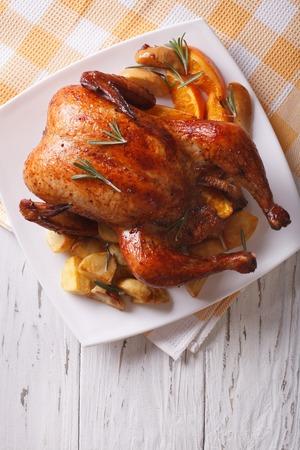 gebakken hele kip met sinaasappels en aardappelen close-up op een bord. verticaal bovenaanzicht