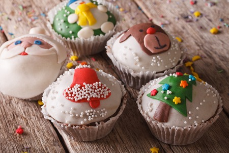 cupcakes: Beautiful festive cupcakes with Christmas decorations close-up on a wooden table.