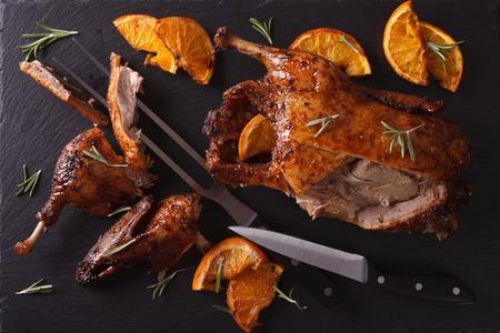 ocas: Cortar el pato asado y las naranjas en un tablero de pizarra de color negro. vista horizontal desde arriba