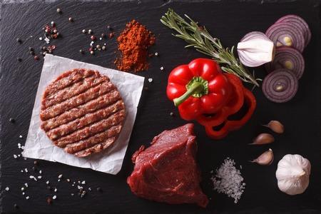 carne macinata cotolette bistecca di carne hamburger crudo con ingredienti sulla scheda. vista orizzontale dall'alto primo piano