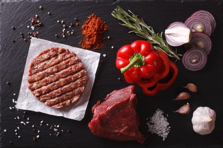 balkan: Raw Ground beef meat Burger steak cutlets with ingredients on the board. horizontal view from above closeup Stock Photo