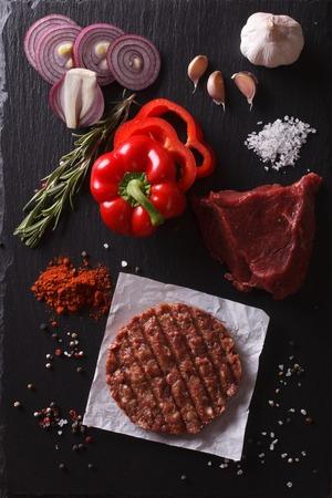 carne de res: Carne molida cruda chuletas hamburguesa de carne de bistec con ingredientes en la pizarra. visión vertical desde arriba