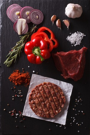 grounds: Raw Ground beef meat Burger steak cutlets with ingredients on the board. vertical view from above Stock Photo