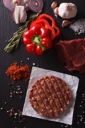 Raw Ground beef meat Burger steak cutlets with ingredients on the board closeup. vertical view from above Stock Photo