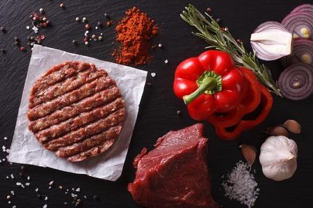 La carne molida chuletas de carne hamburguesa de carne sin procesar con los ingredientes en el tablero. vista horizontal desde arriba