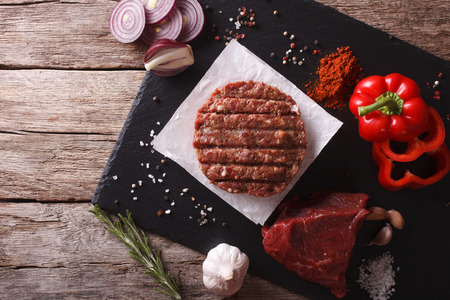 Raw burgers cutlets with the ingredients on the table. horizontal view from above Foto de archivo