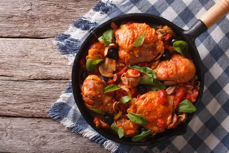 Cacciatori Chicken with mushrooms and black olives in a frying pan. horizontal top view Imagens - 48296229