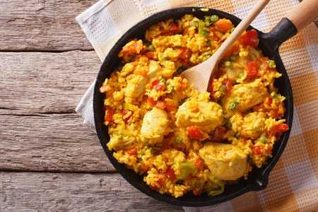 Hispanic cuisine: Arroz con pollo in a frying pan on the table. horizontal top view Banco de Imagens