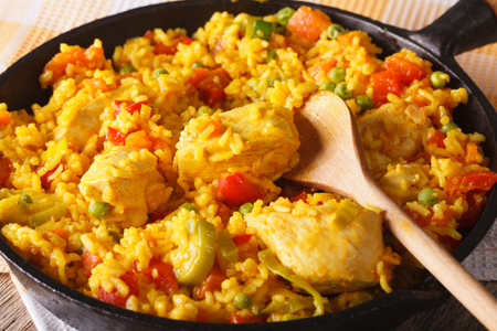 Arroz con pollo - rice with chicken and vegetables in a frying pan macro.