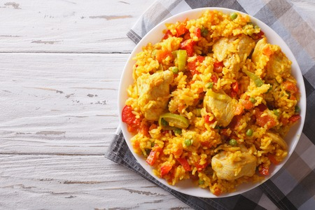 Hispanic cuisine: Arroz con pollo close up in a bowl on the table. horizontal top view