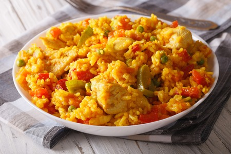 Hispanic cuisine: Arroz con pollo - rice with chicken close up in a bowl on the table. Stock Photo