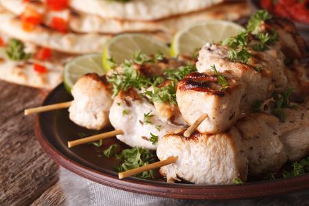 kebab: Indian chicken tikka kebabs on skewers macro on a plate.