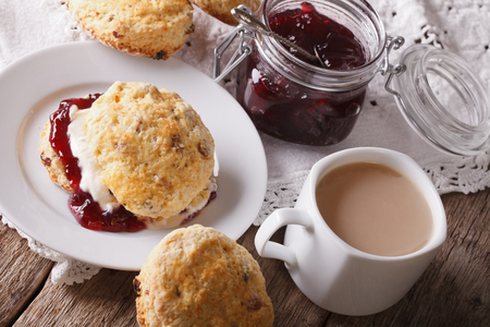 scones: Homemade scones with jam and tea with milk close-up on the table. horizontal