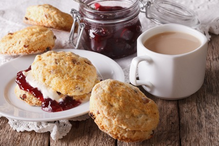 english food: Scones with jam and tea with milk close-up on the table. horizontal