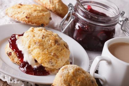 mermelada: pasteles en inglés: bollos con mermelada y té con leche en primer plano en la tabla. Horizontal
