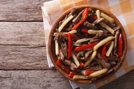 Peruvian cuisine: Lomo saltado on a plate. horizontal view from above, rustic Stock Photo