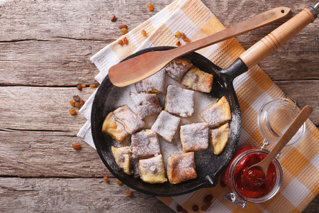 Delicious omelette Kaiserschmarrn with plum sauce on a frying pan. horizontal top view