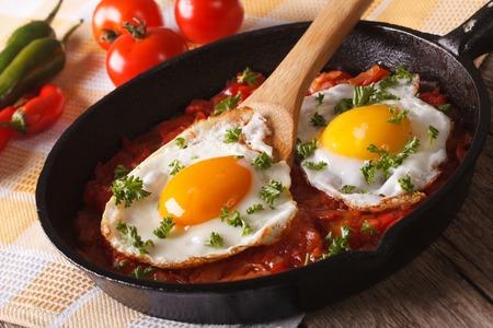 Mexicaans ontbijt huevos rancheros: gebakken ei met salsaclose-up in de pan. Horizontaal Stockfoto