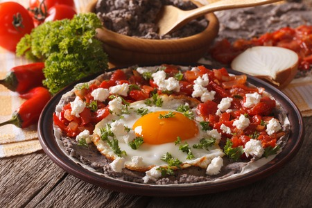 Mexican food: huevos rancheros close-up on a plate on the table. Horizontal