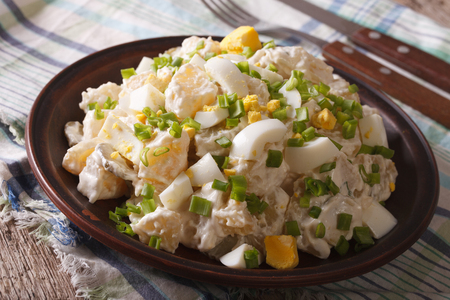 Salad of potatoes, eggs, green onions and mayonnaise on a plate closeup. horizontal