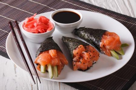 Japanese Salmon temaki sushi, pickled ginger and sauce closeup. horizontal
