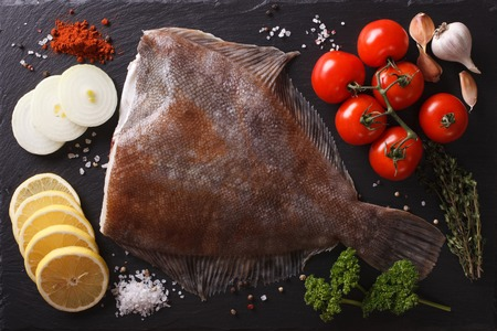 plaice: Fresh raw plaice with ingredients on a slate board closeup. horizontal view from above Stock Photo