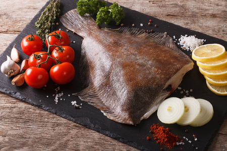 Fresh raw plaice with ingredients on a slate board on a table close-up. horizontal