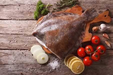 raw flounder with ingredients on a cutting board on a table. Horizontal top view
