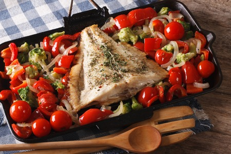 plaice: flatfish with vegetables close-up on a frying pan on the table. Horizontal Stock Photo