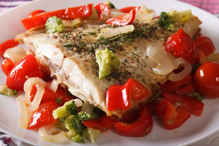 plaice: Baked plaice with peppers and broccoli close-up on a white plate. horizontal