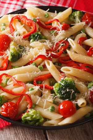 primavera: Pasta Penne Primavera with vegetables close-up on a plate. Vertical Stock Photo