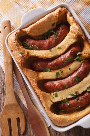 comida inglesa: English food: toad in the hole into a baking dish close up on the table. Vertical top view