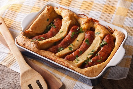 comida inglesa: alimentos Inglés: sapo en el agujero en un molde para hornear de cerca en la tabla. Horizontal Foto de archivo