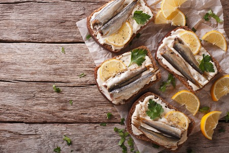 sprats: Toasts with sprats, cream cheese and lemon on the table. Horizontal view from above Stock Photo