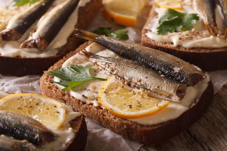 sprats: Tasty fish sandwiches with sprats, cream cheese and lemon macro on the table. horizontal
