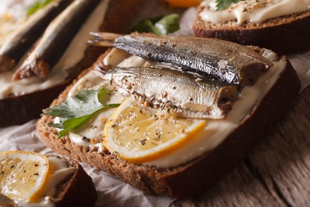 salty: Delicious fish Sandwiches with sprats and cream cheese close-up on the table. horizontal