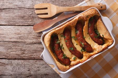 comida inglesa: alimentos Ingl�s: sapo en el agujero en una fuente de horno sobre la mesa. vista superior horizontal