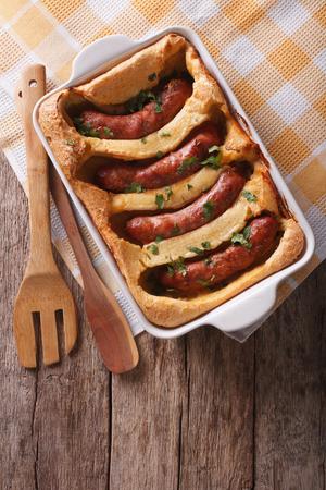 comida inglesa: alimentos Inglés: sapo en el agujero en una fuente de horno sobre la mesa. vista superior vertical Foto de archivo