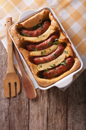 english food: English food: toad in the hole into a baking dish on the table. Vertical top view