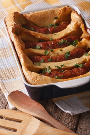 comida inglesa: alimentos Ingl�s: deliciosas salchichas en una fuente para horno de cerca en la tabla. vertical Foto de archivo