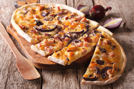 Delicious sliced pie flammkuchen with bacon and red onion close-up on the table. horizontal Stock Photo