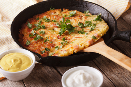 Potato rosti with herbs close-up in a frying pan on the table. Horizontal Banco de Imagens