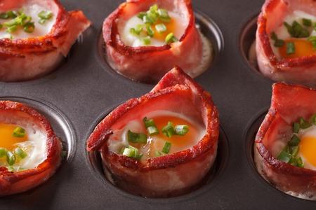 Recién horneados huevos calientes envueltos en tocino de cerca en un plato para hornear. Horizontal Foto de archivo - 49858968